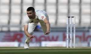 England's Mark Wood falls on the ground after bowling a delivery.