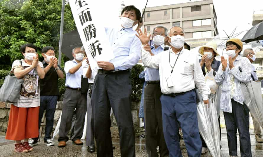 A group of supporters for plaintiffs celebrate, holding a banner that reads 'Overall victory' outside the Hiroshima district court in western Japan.