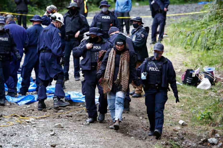 Police escort a protester away after their arrest for blocking a logging road on southern Vancouver Island, in British Columbia, Canada.