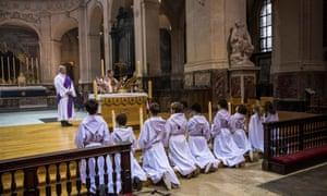 Altar boys attend mass at Saint Roch Church in Paris, France.