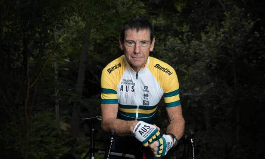 Roger Cull wearing professional biking gear in Australian colours, staring directly at the camera