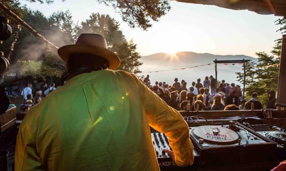 A DJ performs in front of a crowd at the Meadows in the Mountains festival, Bulgaria, in the distance the sun sets on the mountains.