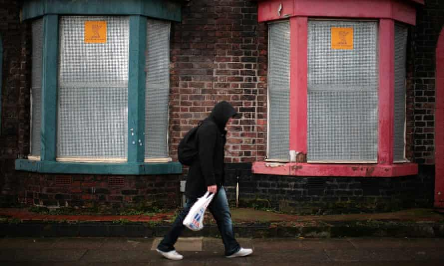 Man walks past derelict housing