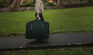 A Syrian refugee carries his luggage to his new home in Rothesay on Bute.
