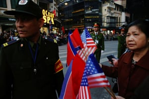 A woman holds North Korean and US flags