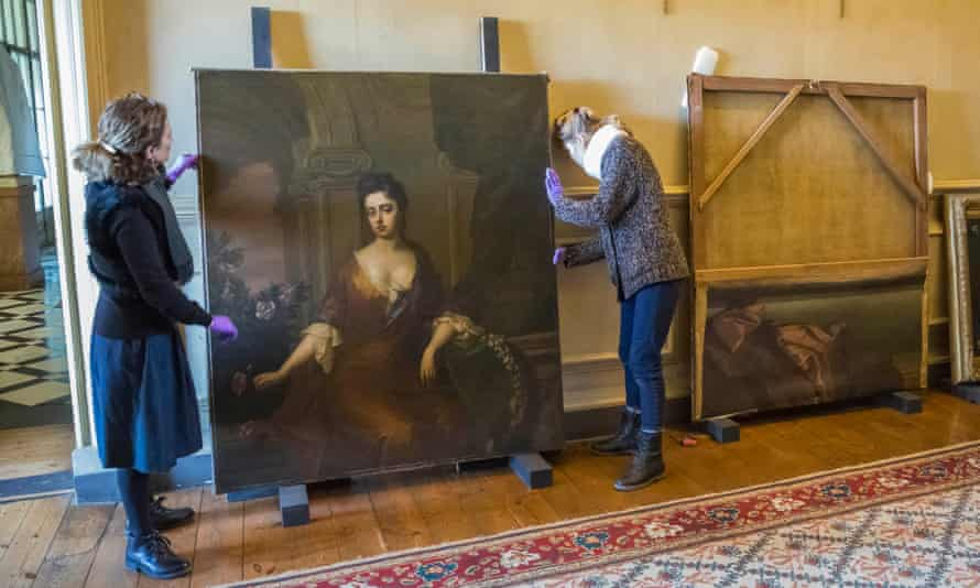 The two portraits under restoration, showing the area of canvas including the legs cut and tacked on to the back of the frame.