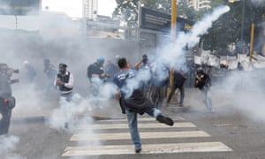 An anti-Maduro demonstrator throws teargas back at police in Caracas. Mass gatherings have now been banned in Venezuela.