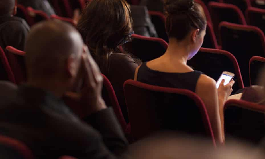 Rear view of woman using phone in theatRE audience