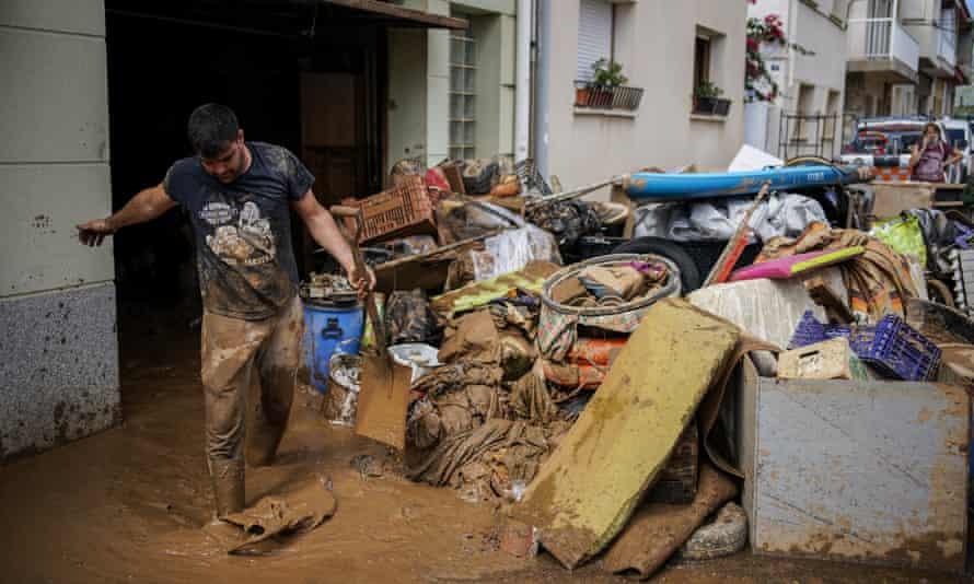 Un hombre quita el barro después de una inundación.