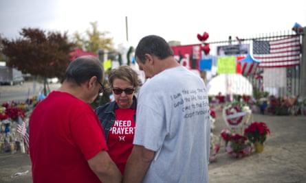 People pray at a makeshift memorial set up near the Inland Regional Center in San Bernardino.