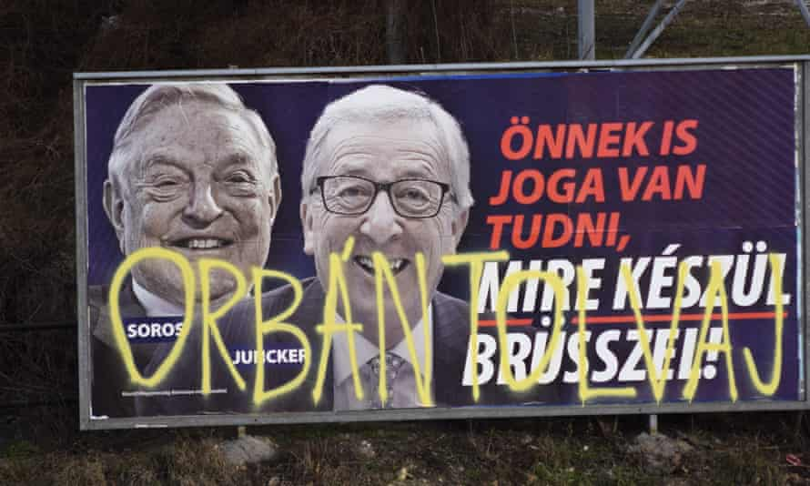 A billboard in February 2019 from a campaign of the Hungarian government showing EU Commission President Jean-Claude Juncker and Hungarian-American financier George Soros sprayed with graffiti saying 'Orban thief,' in reference to Hungarian Prime Minister Viktor Orban. (AP Photo/Pablo Gorondi)
