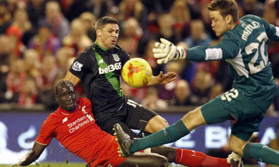 Liverpool's Mamadou Sakho vies for the ball with Stoke's Jon Walters as Simon Mignolet makes a save during the Capital One Cup semi-final