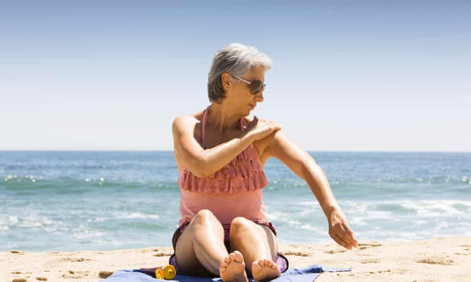 A woman on a beach applying sunscreen