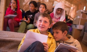 Children attend an English lesson inside a tent at the makeshift camp at the Greek-Macedonian border, near the village of Idomeni