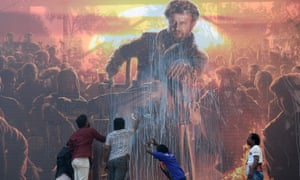 Fans splash milk on a billboard displaying the Bollywood star Rajinikanth before a show of the Tamil-language film 'Pettai' in Chennai this month.