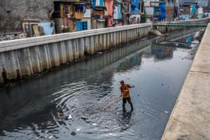 A worker cleans up trash on a recently revitalised river in West Jakarta.