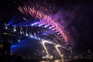 The midnight fireworks light up the Sydney Harbour Bridge