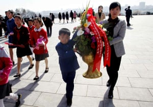 People carry flowers to pay tribute