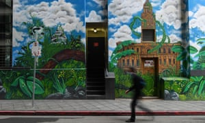 A person wearing a face mask walks past a street art mural in Melbourne.