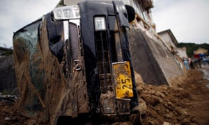 A car is left upturned after torrential rain caused a landslide in Kumano.