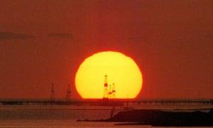 The sun rises over oil rigs at the shore of the Caspian Sea off of Baku, Azerbaijan.