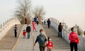 People walk in a park in Beijing