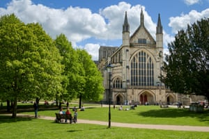 Winchester Cathedral, Hampshire, England, UK - with people relaxing in the park