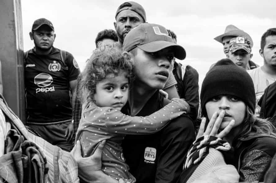 Families wait patiently in front of the closed gates of the border crossing between Guatemala and Mexico