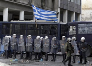 A Greek flag waves on a police vehicle as riot police guard the agriculture ministry