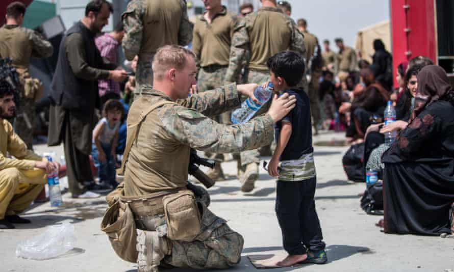 A United States Marine gives a child water at Hamid Karzai International Airport, Kabul