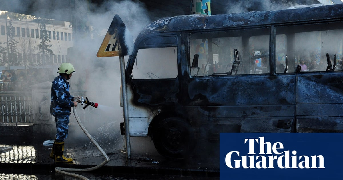 Charred wreckage of army bus after bombing kills 14 in Damascus – video