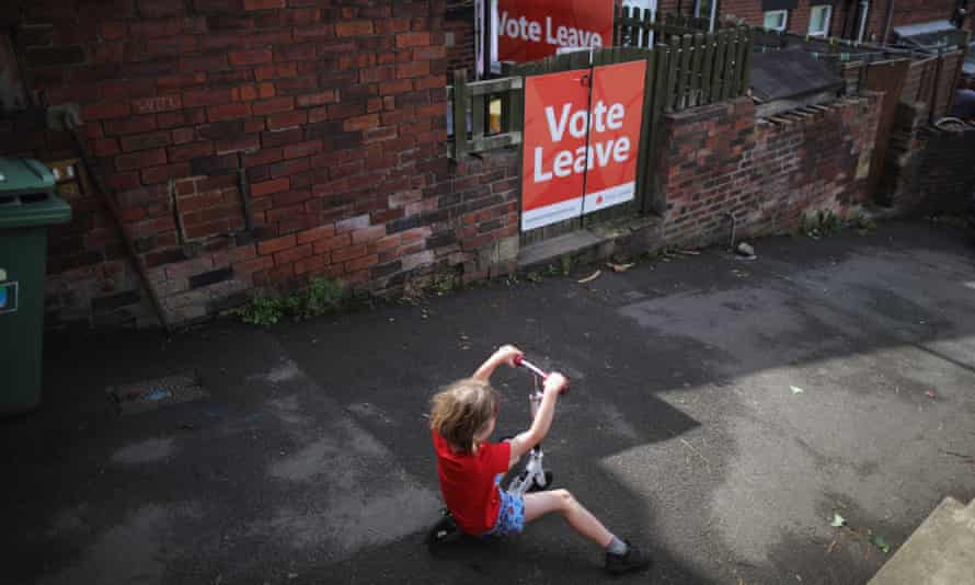 A young child rides a scooter past a 'Vote Leave' poster in the back alley in Batley, West Yorkshire