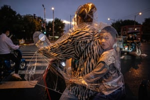 A boy sits inside his mother's plastic raincoat as they wait to cross at a traffic light during a rainstorm in Beijing.