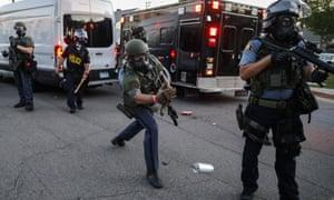 A police officer tosses a tear gas canister towards protestors on Hamline Avenue on Thursday.