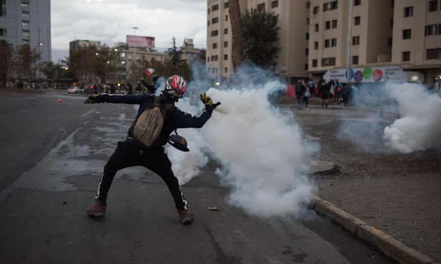 A demonstrator clashes with security forces during a protest amid the coronavirus pandemic in Santiago on 27 April.