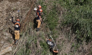 Rescuers use a line to transport a body recovered at the Itogon site where victims are believed to have been buried