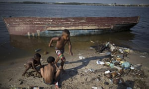 Boys play next to an abandoned boat, on the garbage-littered shore of Guanabara Bay in Rio.
