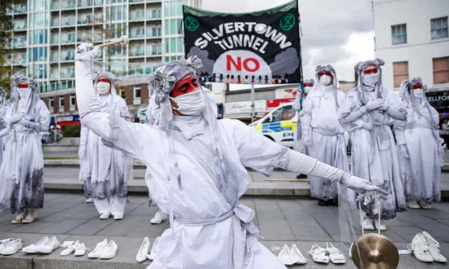 Protesters in fancy dress stand in front of an anti-tunnel banner, with pairs of white shoes laid out neatly in a row on the pavement