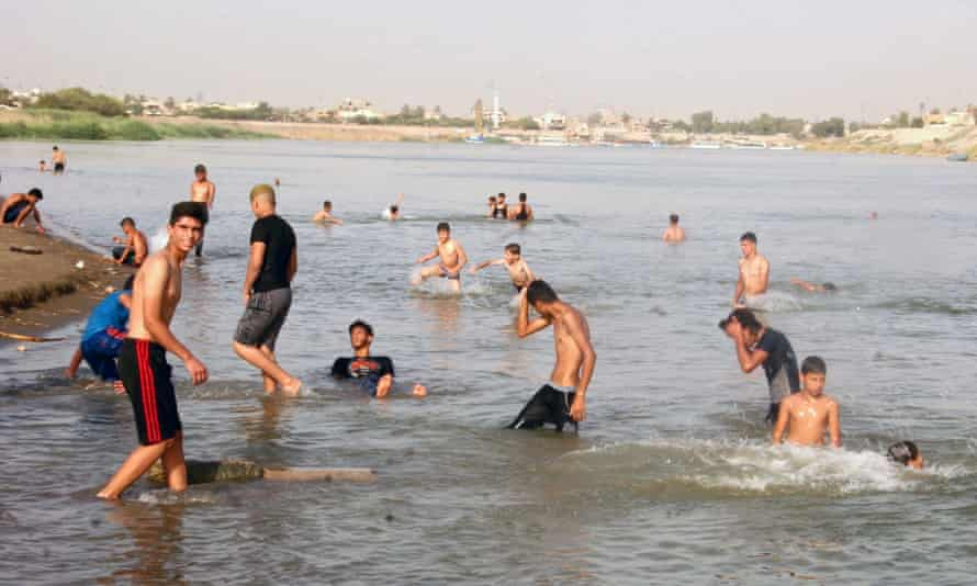 Iraqis swim to cool themselves in the Tigris river in Baghdad, Iraq, where temperatures are expected to reach 49C this week
