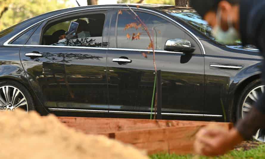 Parents watch burial from car