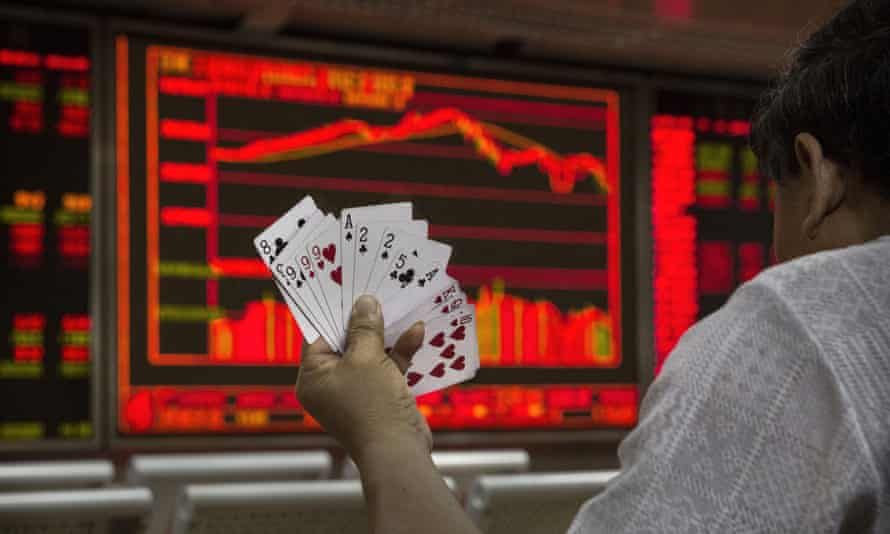 A Chinese trader holds a set of cards in his hand as he watches a stock ticker in Beijing.