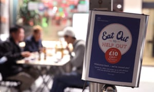 diners in soho, London, with an eat out to help out poster in the foreground