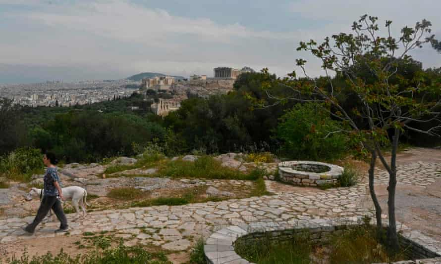 A woman walks her dog at an empty touristic spot in Athens overlooking the Ancient Acropolis and Athens city on 21 April.