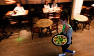 A waitress serves pizza at a restaurant in Moscow