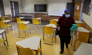 A worker walks past safely spaced desks following safe distancing measures amid the spread of the coronavirus disease outbreak at the Seshegong secondary school in Olivenhoutbosch, South Africa, May 28, 2020.