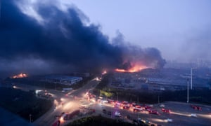 Fire and smoke rises at the site of the massive explosions in Tianjin