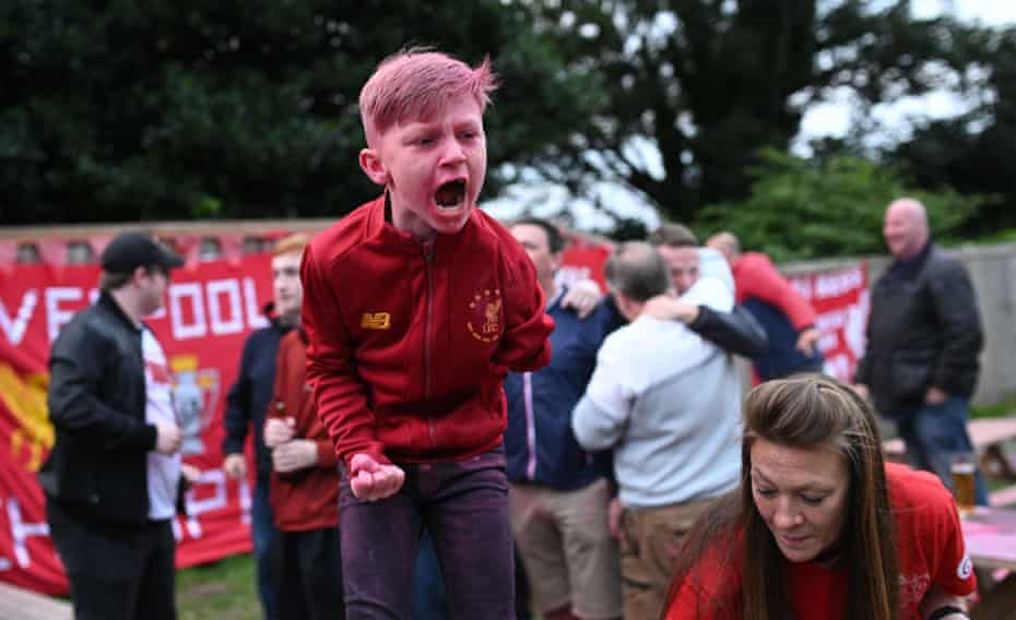 Young football fan celebrates Liverpool's Premier League victory