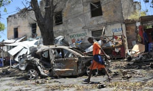 A boy walks past the site of a car bomb in Somalia's capital, Mogadishu, which killed four people on Thursday.