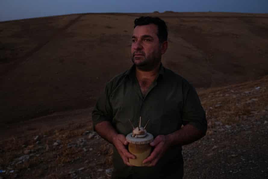 Landmine survivor Rebwar Ali holds an Italian Valmara 69 landmine for a portrait beside the hill where he survived a landmine explosion while posing for a portrait at Biyawele Village near Halabja, Iraqi Kurdistan