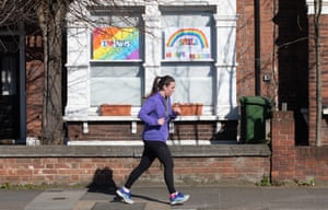 A jogger runs past a house declaring its support for the NHS